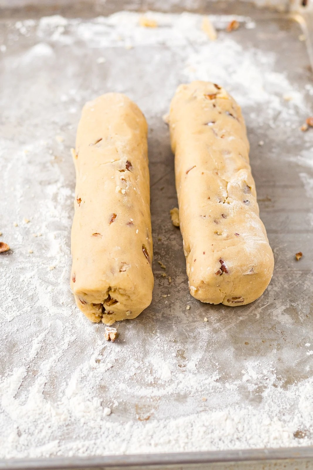 two logs of pecan shortbread dough on a baking sheet before chilling