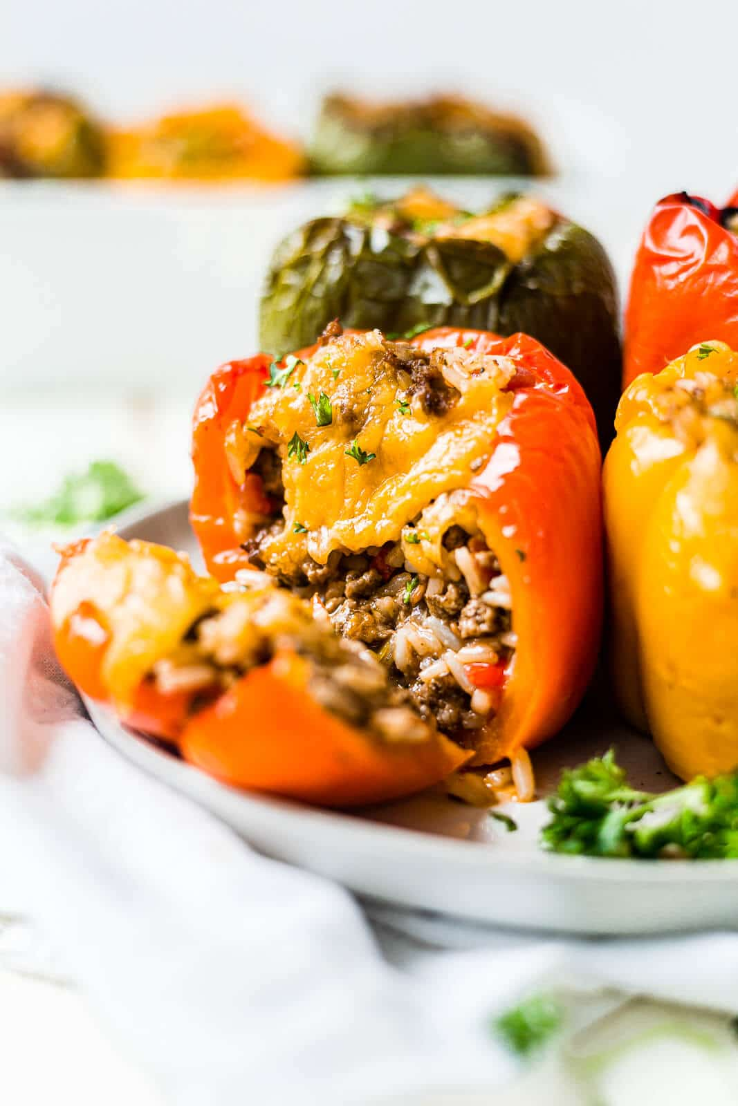 air fryer stuffed peppers in a white plate topped with cheese and parsley with one cut open to see the rice and beef inside