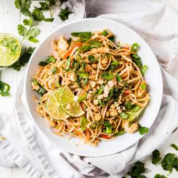 easy chicken pad thai recipe topped with green onion, cilantro and lime wedges in a shallow white bowl