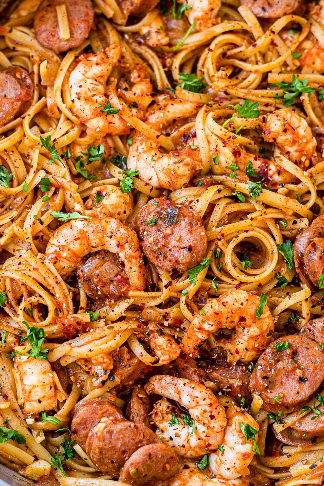 close up of cajun shrimp and sausage pasta with a creamy cajun sauce and fresh parsley