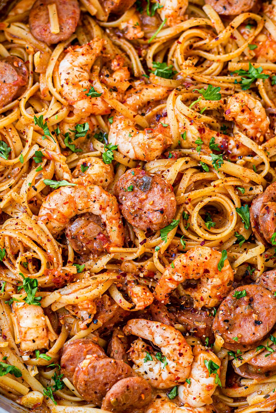 close up of cajun shrimp and sausage pasta with a creamy cajun sauce and fresh parsley