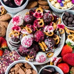 chocolate covered pretzels, cake balls, fruit, popcorn and cookies on a valentine's day dessert board
