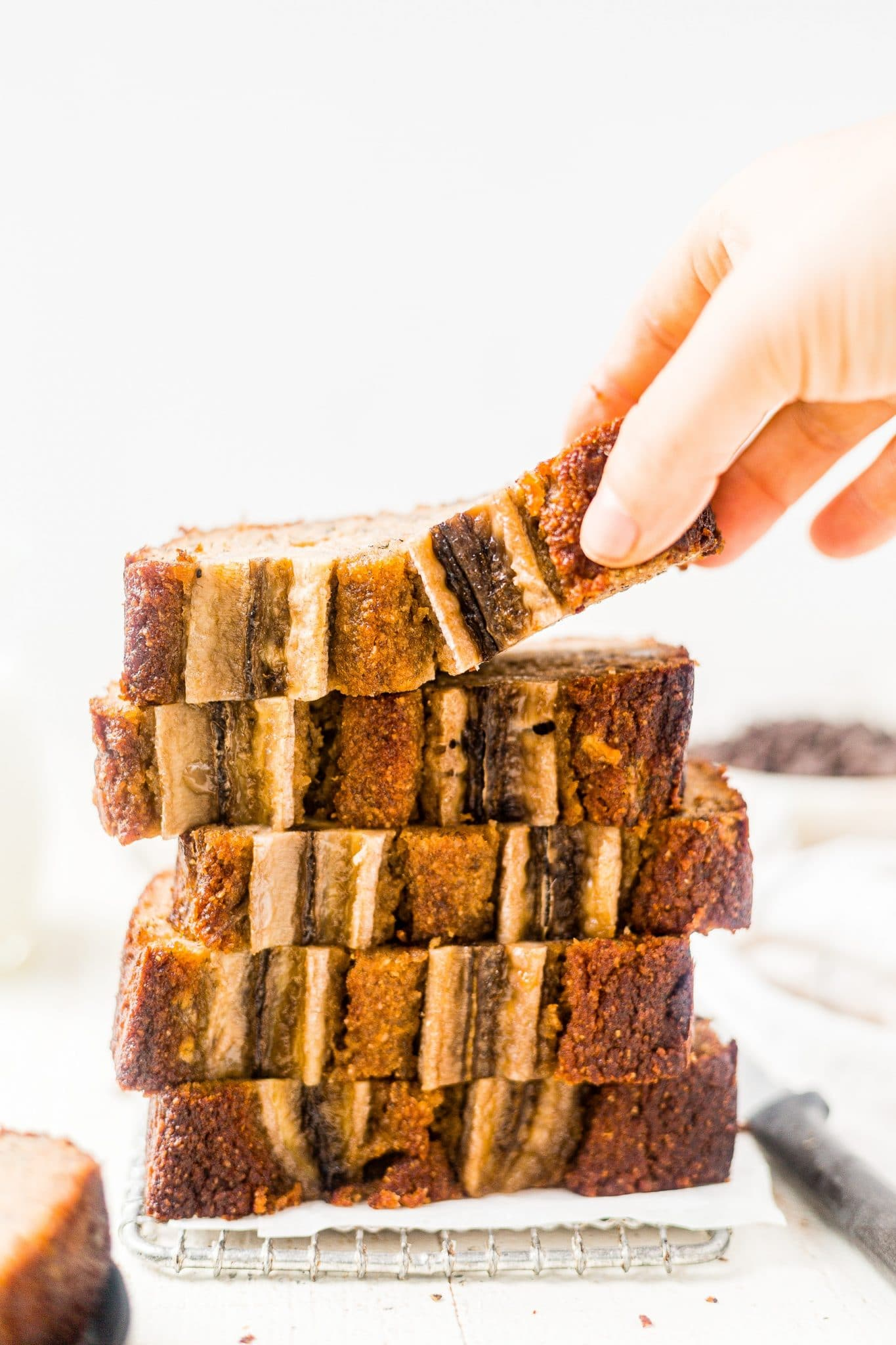 5 slices of banana bread made with almond flour stacked on top of each other with a hand reaching for the top one