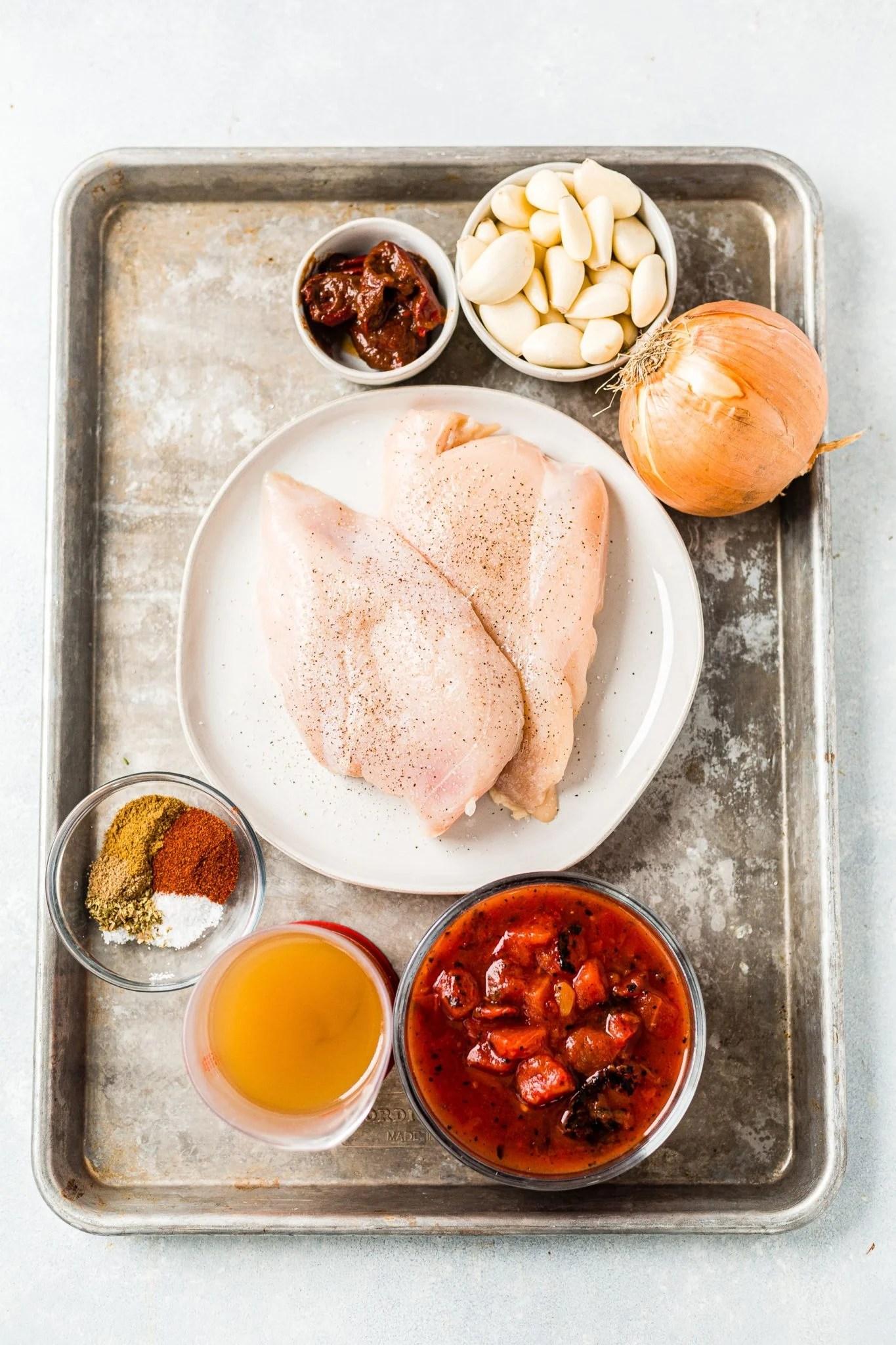 ingredients for chicken tinga arranged on a large sheet pan
