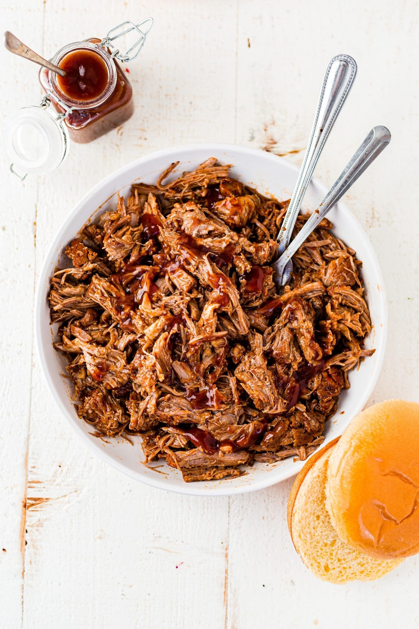instant pot pulled pork tossed in bbq sauce in a large white bowl with 2 serving spoons