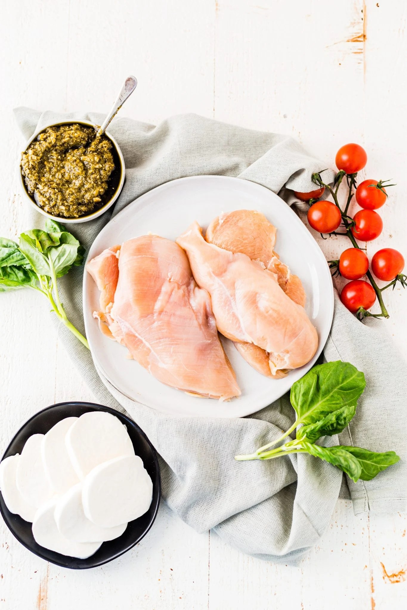 chicken breast, fresh mozzarella and basil pesto on a table before being cooked