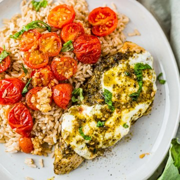pesto chicken covered in melted mozzarella with a side of rice and roasted tomatoes
