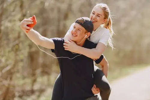 Unusual sports around the world: woman carried on the back by man taking a selfie