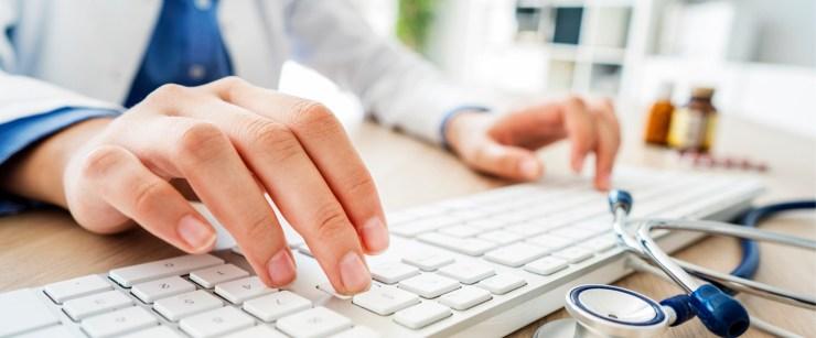 female doctor typing on keyboard