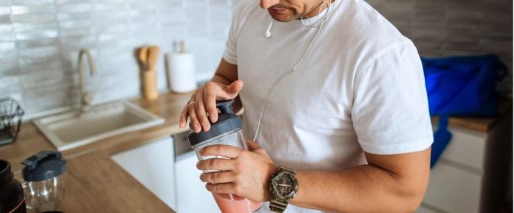 man making protein shake before workout