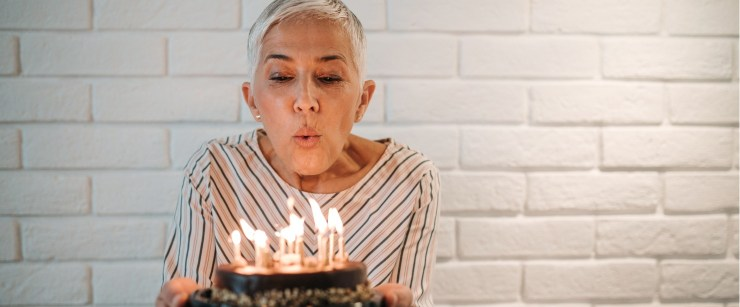 older woman blowing out candles on birthday cake