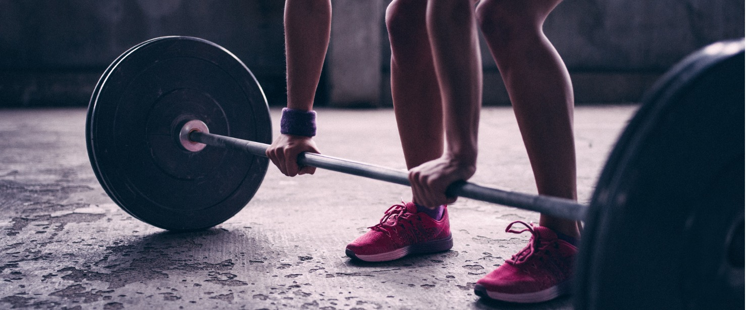 woman gripping barbell with weights on it