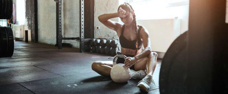 fit woman tired while working out with kettlebell