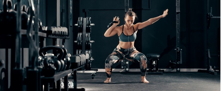strong woman doing kettlebell squat to press