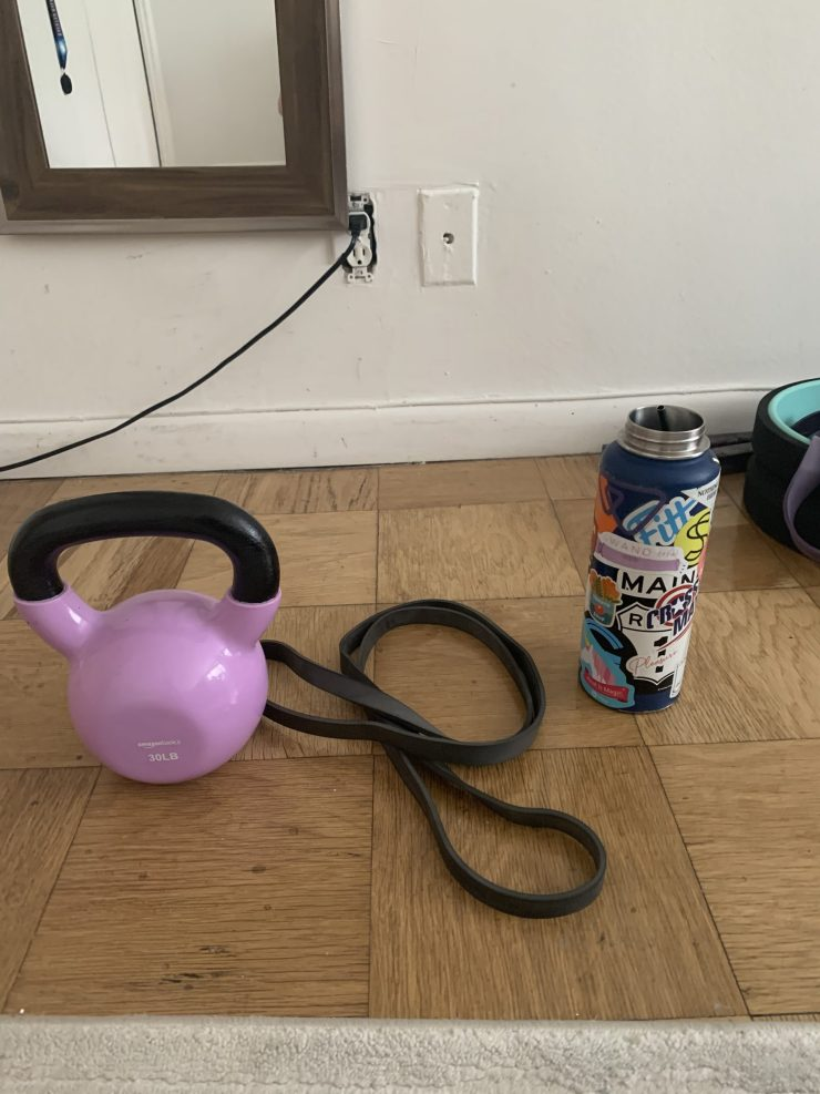 kettlebell with resistance band and water bottle on apartment floor