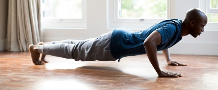 man doing pushups on wood floor at home