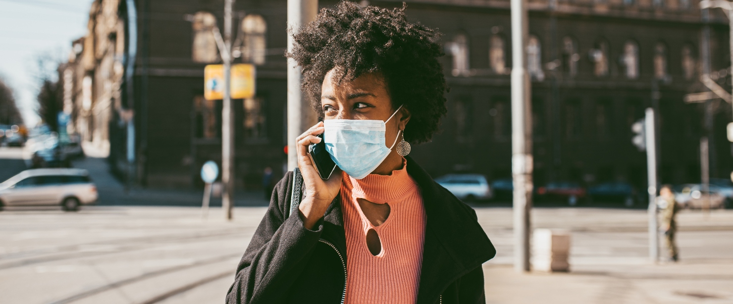 young black woman on the phone outside wearing face mask