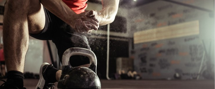 fit man preparing to lift kettlebell in the gym