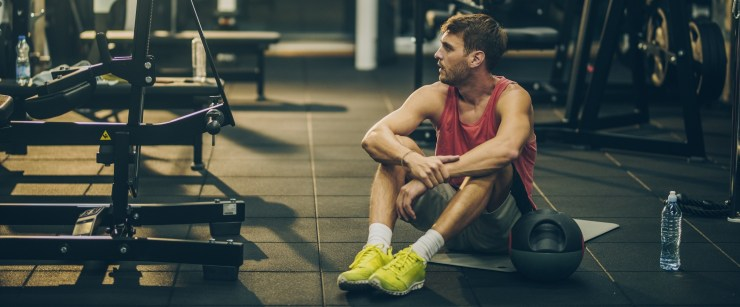 man tired at gym after workout overtraining syndrome