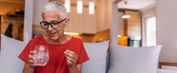 older woman taking supplement