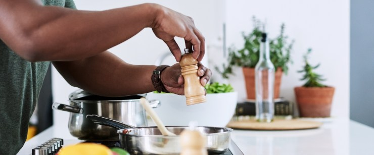 nutrients men fall short on: man seasoning food he's cooking on the stove