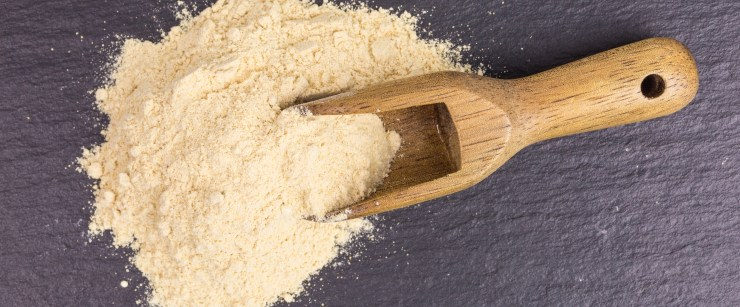 powdered maca root with wooden scoop