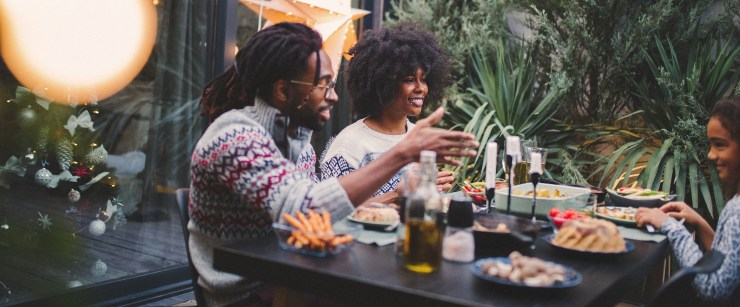 avoid holiday weight gain: young black family eating holiday dinner outside