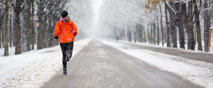 outdoor winter workouts: woman running outside in the snow