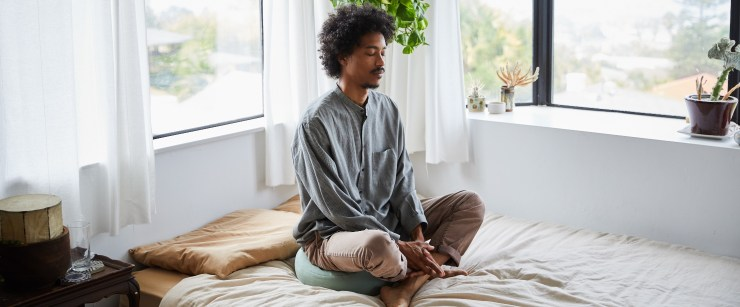 stress support supplements: young black man meditating in bed