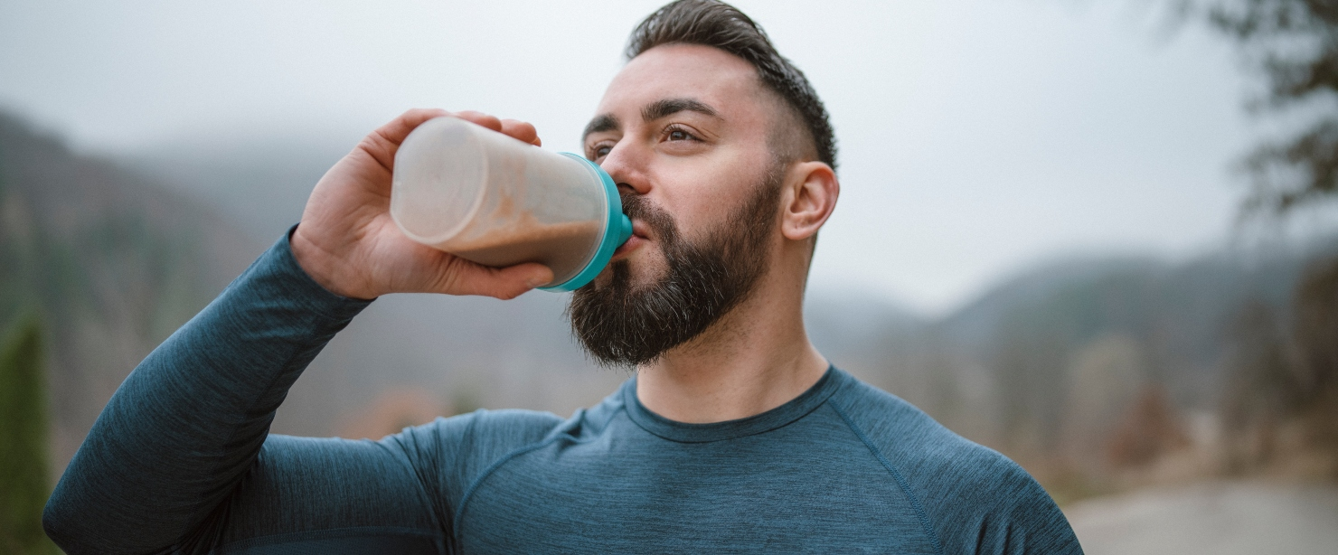fit man drinking protein shake outside