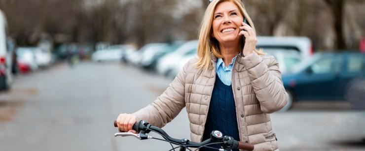 woman walking bike on phone