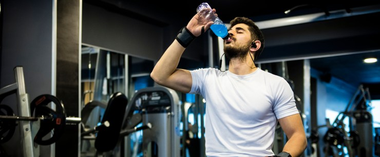 thermogenic pre-workout: man drinking sports drink at gym