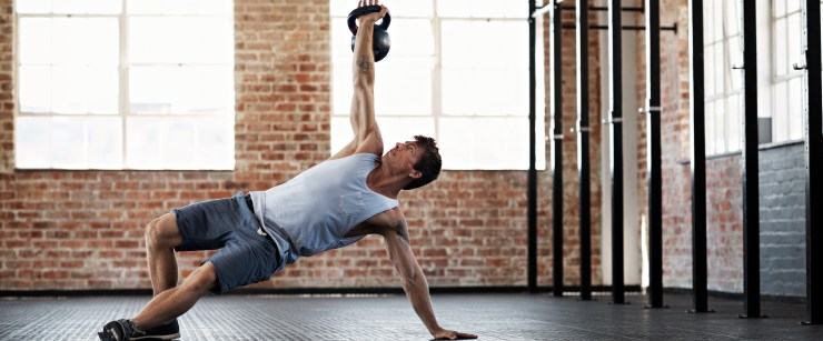 pack on the muscle: young man lifting kettlebell