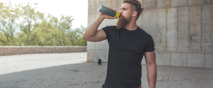 BCAA ratio: man drinking sports drink outside