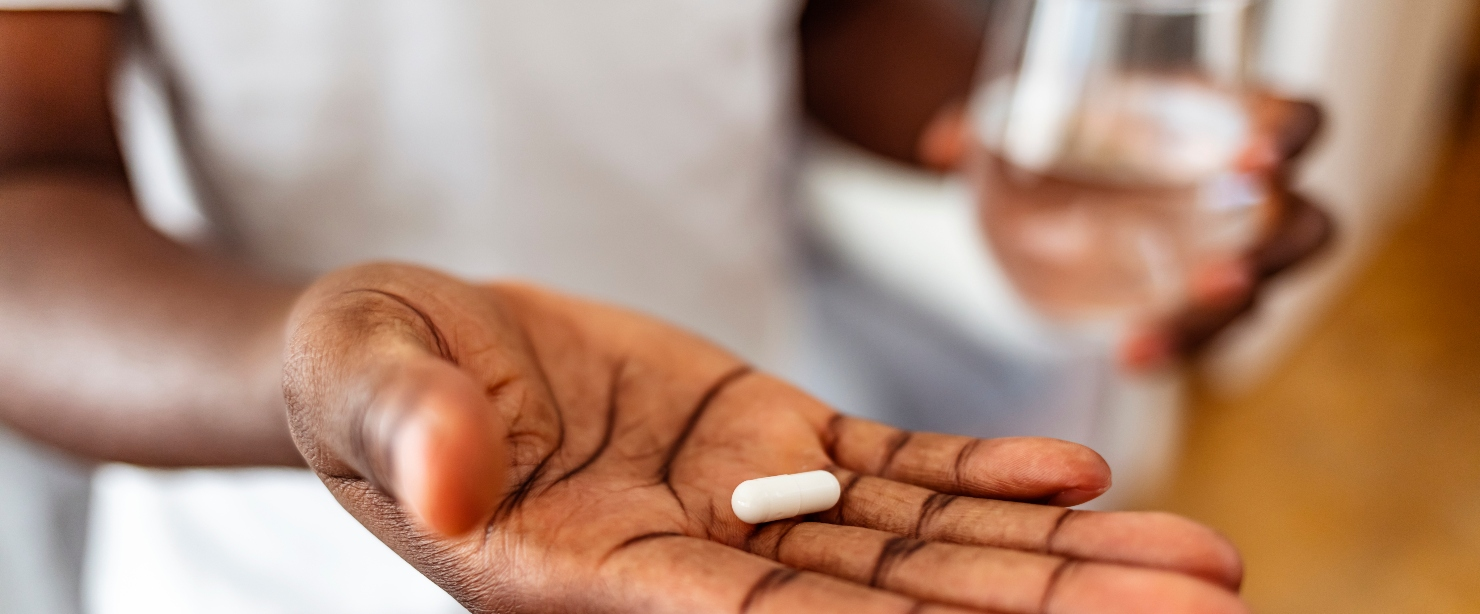 how to take supplements to avoid stomach upset: hand holding pill close up