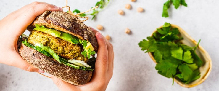 iron on a plant-based diet: hands holding veggie burger