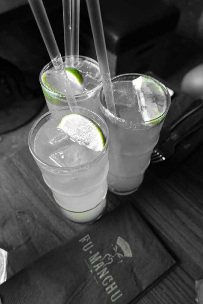 Black and white shot of cocktails with the lime still green