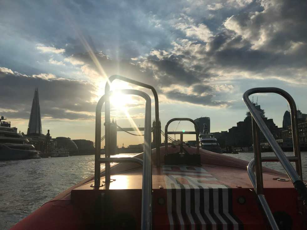 View of London from the Thames Rockets boat with the sun coming out from behind a cloud