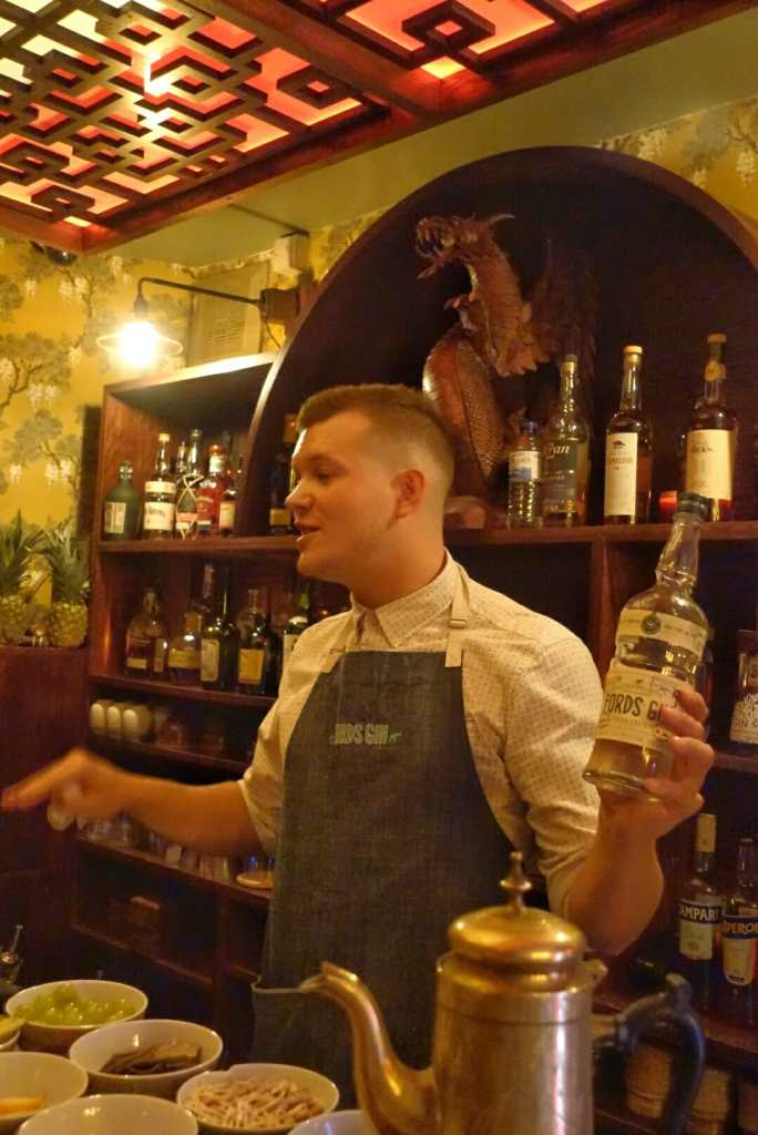 Nick behind the bar holding a bottle of Ford's gin