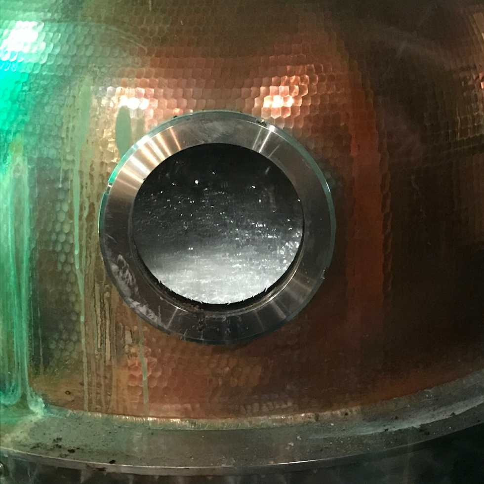 Close up of the alcohol distilling through the still window