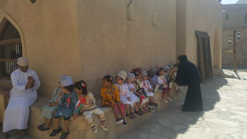 A school group at Nizwa Fort, many of the boys and their teachers are wearing traditional Omani dress