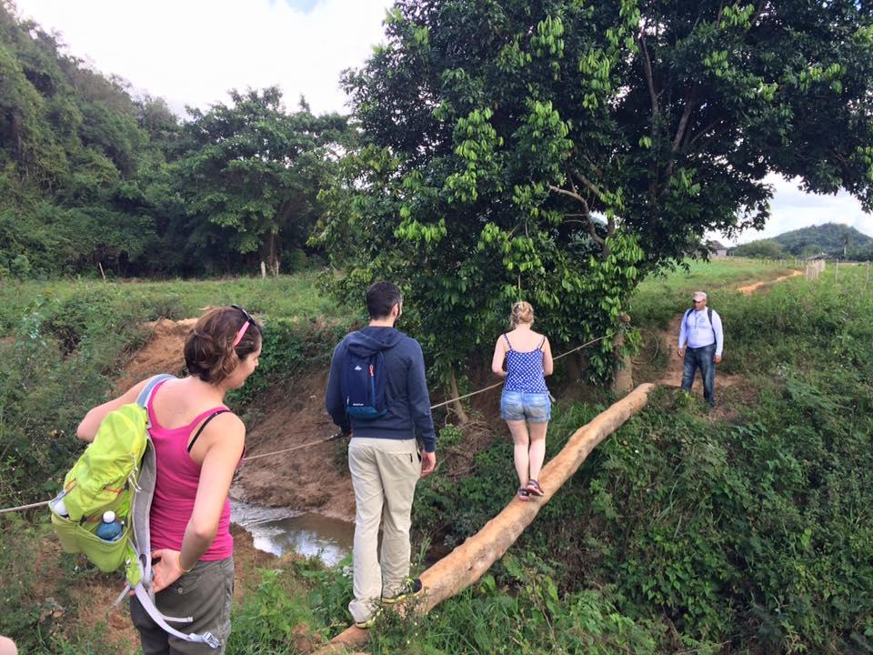 Katie's group crossing a log bridge in Cuba with Cuban Adventures