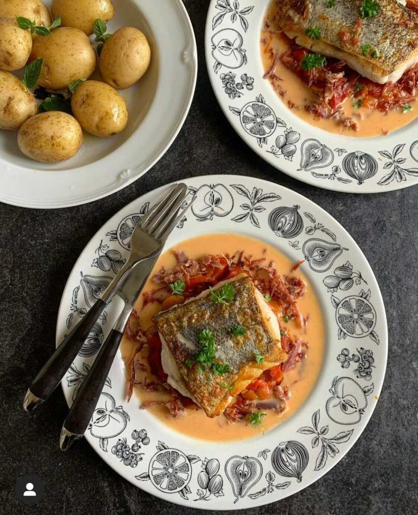 Hake on 2 plates with sauce and garnish and a bowl of new potatoes