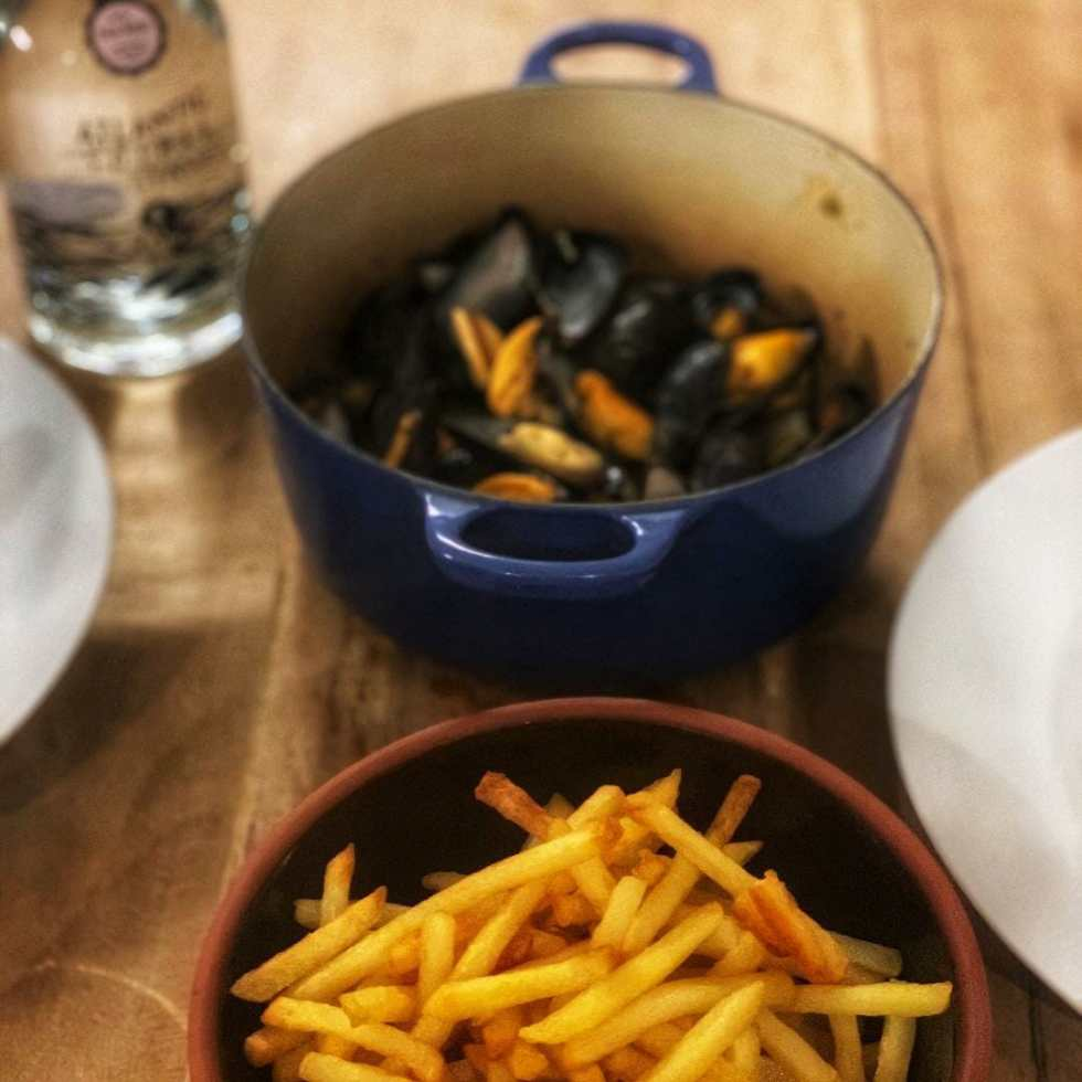 Bowls of mussels and fries with Atlantic Spirits Thai basil gin bottle