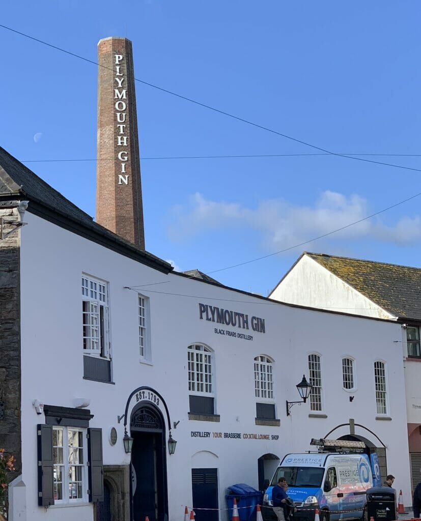 The outside of the distillery on the curve of the road with chimney