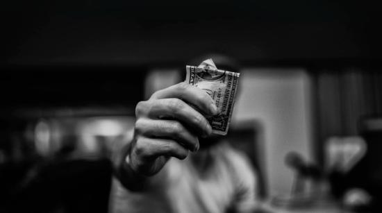 Man Holding Dollar Bill