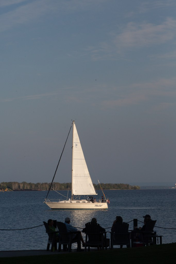 People watching a sailboat in the Duluth Harbor at Pier B Resort