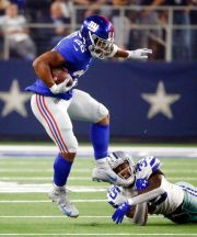 (AP Photo/Michael Ainsworth). New York Giants running back Saquon Barkley (26) runs past Dallas Cowboys defensive back Kavon Frazier (35) during the first half of an NFL football game in Arlington, Texas, Sunday, Sept. 16, 2018.