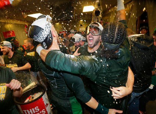 A's clinch playoff berth, then beat Mariners 7-3
