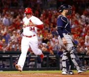 (AP Photo/Jeff Roberson). St. Louis Cardinals' Yairo Munoz (34) scores past Milwaukee Brewers catcher Manny Pina during the third inning of a baseball game Monday, Sept. 24, 2018, in St. Louis.